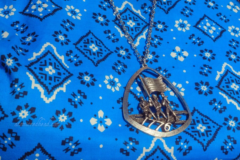 """Close-up of my necklace, which features """"The Spirit of '76"""" three men, one carrying the American flag, another a drum, another with a flute. Text reads """"1776"""" along the bottom."""