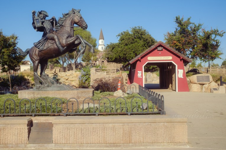 A statue of Paul Revere atop a rearing horse stands in front of a small covered bridge which gives way to the small New England themed island.
