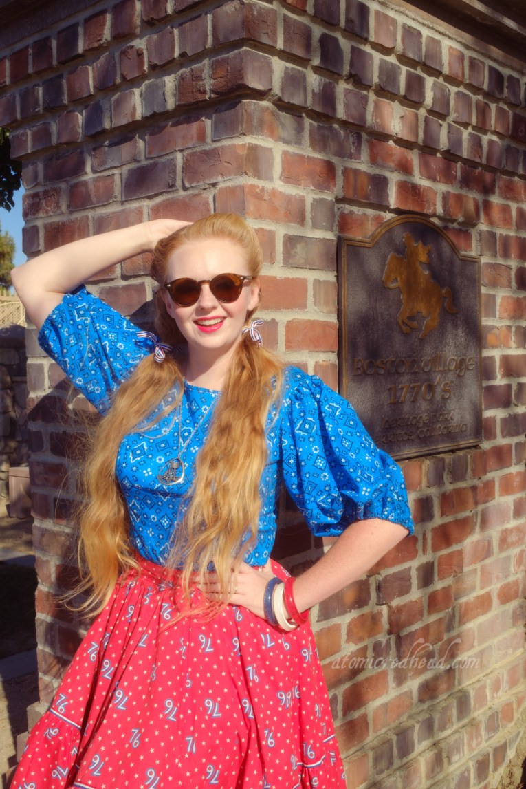 """Myself, wearing a blue peasant top with a bandana print on it, a red skirt with """"76"""" in white scattered throughout, and white shoes, standing in front of a brick pillar with a bronze plaque featuring the silhouette of a man on horseback, and text reading """"Boston Village 1770s Heritage Park Cerritos California"""""""