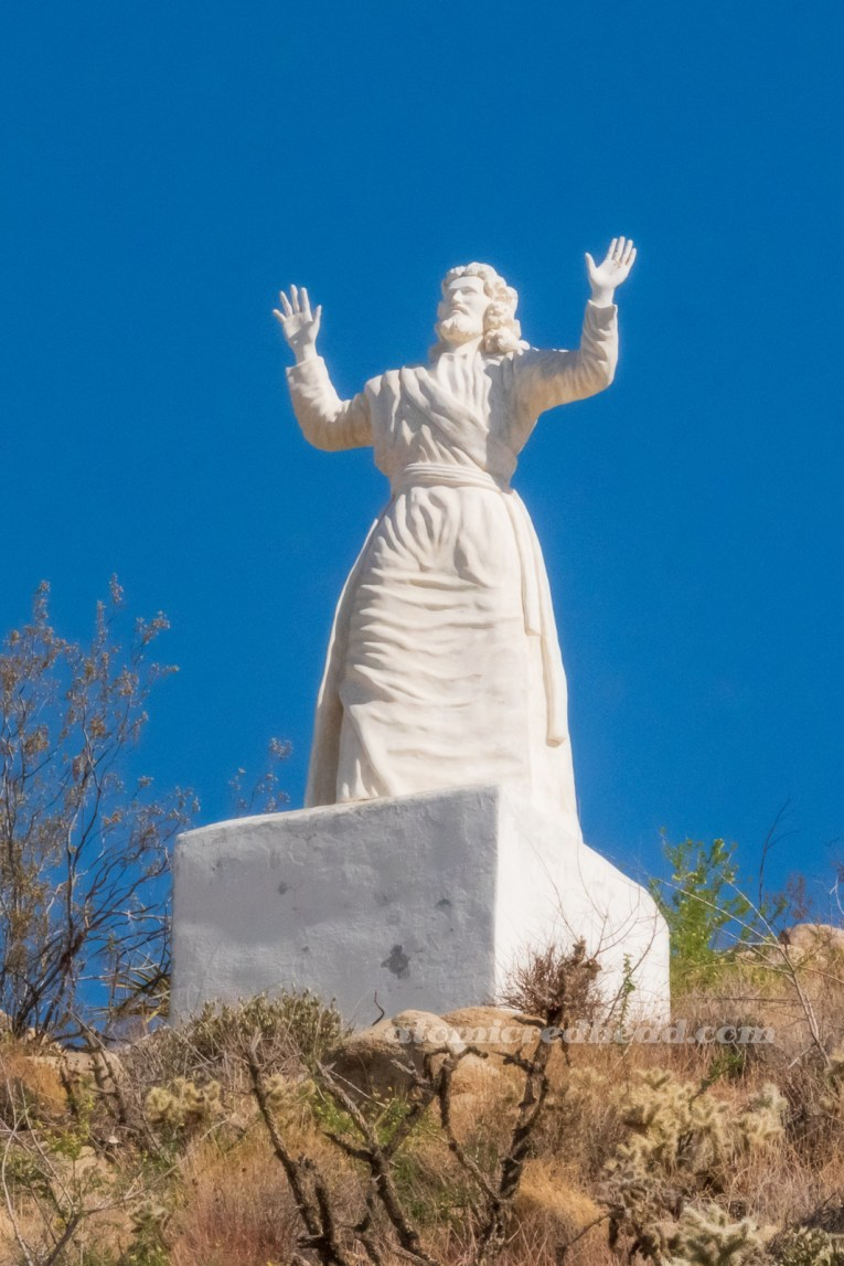 """The """"Unwanted Christ."""" A massive white washed statue of Jesus with his hands lifted toward the sky."""
