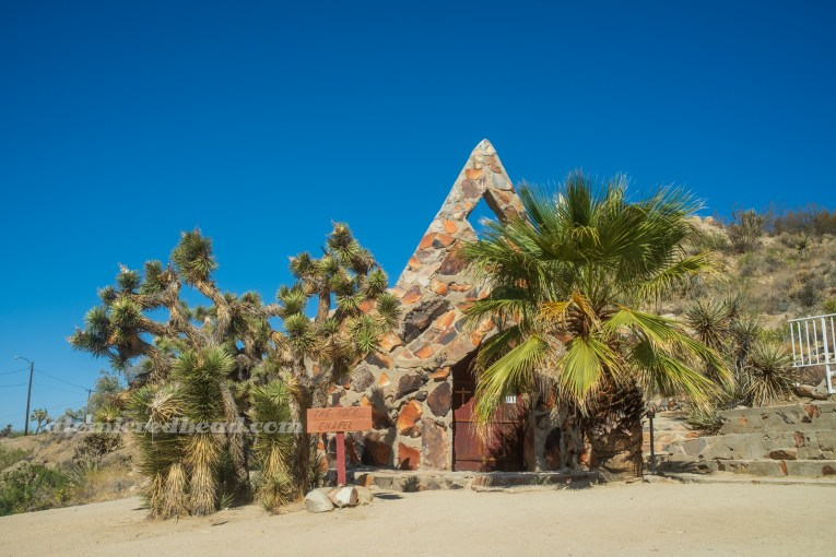 A small church made of warm rock and concrete. It has a flat triangle shaped steeple and palm trees out front.