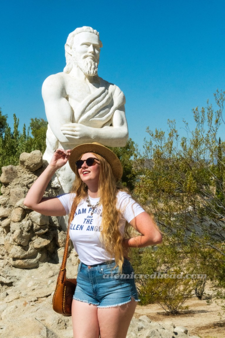 Myself, wearing a straw hat, a white shirt reading 'Gram Parsons and the Fallen Angels' in blue text, blue jean shorts, standing in front of a massive white washed statue of a bearded man.