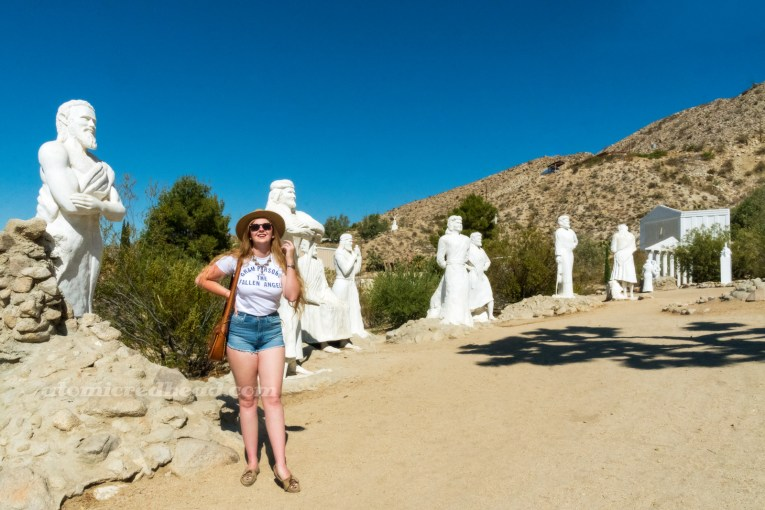 Myself, wearing a straw hat, a white shirt reading 'Gram Parsons and the Fallen Angels' in blue text, blue jean shorts, standing in front of a row of giant white washed statue of people.
