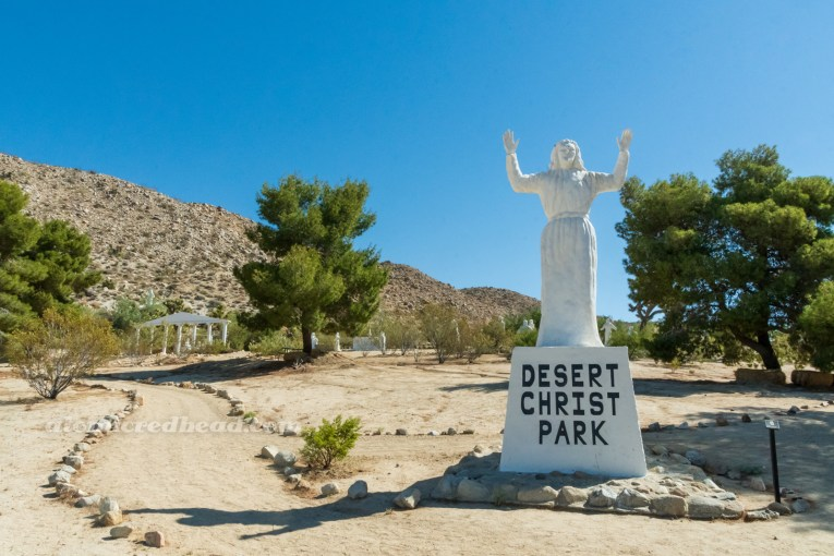 """A white washed statue of Jesus with his hands raised, on the base in black text reads """"Desert Christ Park."""""""