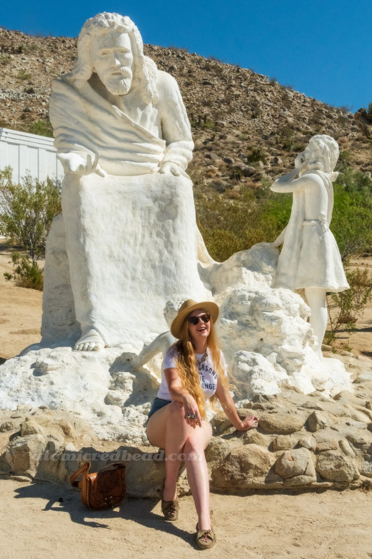 Myself, wearing a straw hat, a white shirt reading 'Gram Parsons and the Fallen Angels' in blue text, blue jean shorts, seated at the base of a massive white washed statue of Jesus, who is seated and extends his hand.