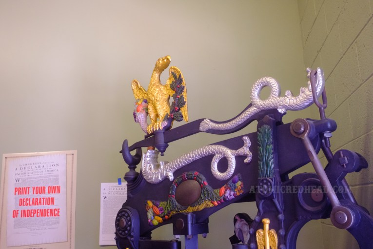 Close-up of detail of a printing press which features a gold eagle.