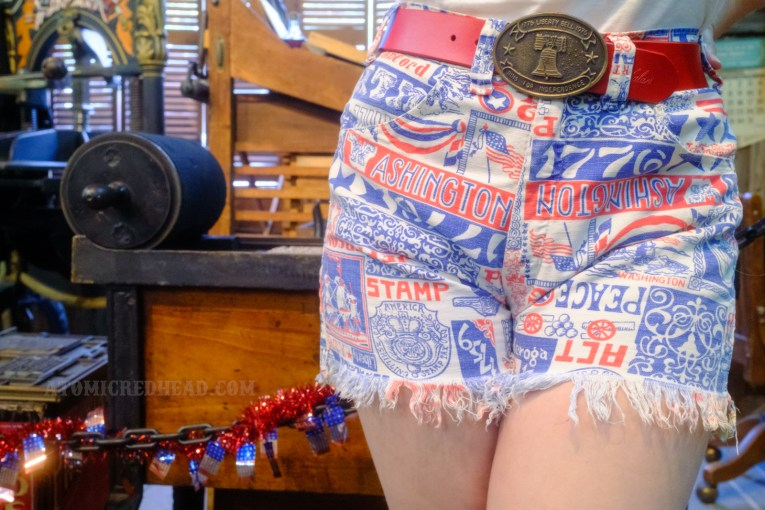 """Close-up of my shorts. A red belt features a bronze belt buckle featuring an image of the Liberty Bell and text reading """"1776 Liberty Bell 1976 Ring for Independence"""" the shorts are white with various text and images in red and blue. Words such as """"Washington,"""" """"Stamp Act,"""" """"Peace,"""" """"1776,"""" """"Concord,"""" and """"Jefferson"""" are intermixed with images of Washington crossing the Delaware, cannon, American flag, stars, and ships."""