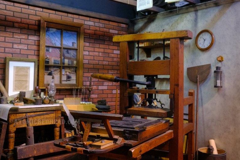 An antique press sits in a mock up of Benjamin Franklin's print shop.