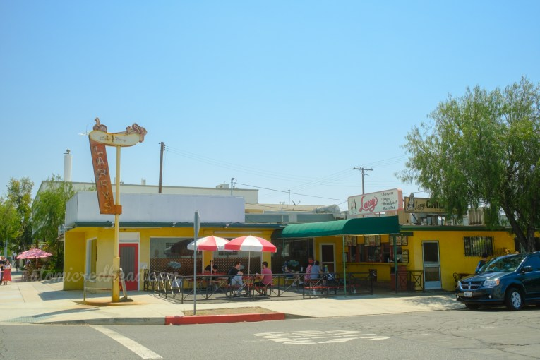 """The Larry's neon sign sits at the corner of a fenced off outdoor eating area for Larry's, which features several picnic tables with red and white umbrellas near the outdoor order and pick-up windows. A large sign on the roof features a cartoon dog and reads """"Larry's"""""""