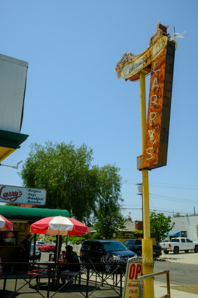 """The Larry's neon sign sits at the corner of a fenced off outdoor eating area for Larry's, which features several picnic tables with umbrellas near the outdoor order and pick-up windows. A large sign on the roof features a cartoon dog and reads """"Larry's"""""""