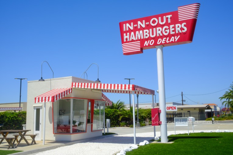 """Replica of the first In-N-Out, a small, ten foot by ten foot white box, with red and white stripe awnings, a white rock horseshoe driveway curves up to the building. A tall sign to the right reads """"In-N-Out Hamburger No Delay"""" in neon."""