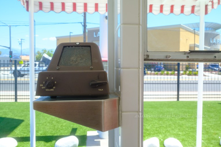 Located to the left of the window is a small brown speaker, used to communicate with the customer to take their order.