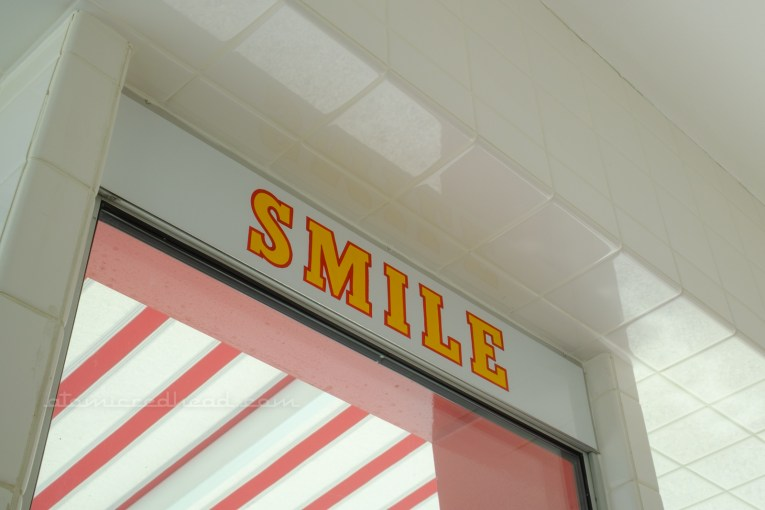 """Close-up of yellow letters edged in red reading """"Smile"""" located above the service window."""