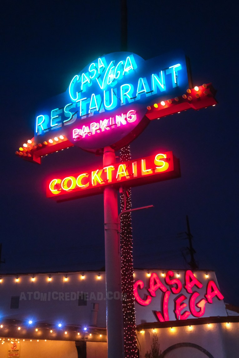 """Shot of the multi-color neon sign, reading """"Casa Vega Restaurant"""" in blue neon, """"Parking"""" in pink, and """"Cocktails"""" in red."""