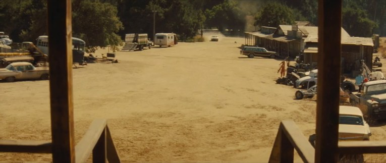 Screencap from Once Upon a Time...In Hollywood, the view from the porch of George Spahn's house, with western buildings on the right, and various cars scattered about.