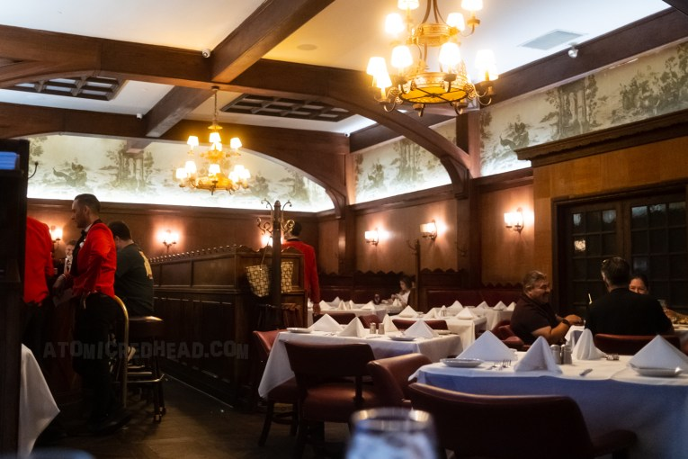 Interior of Musso & Frank's today, with dark wood walls and tables and chairs, the tables are laid with a white table cloth. Waiters wear smart red velvet jackets.