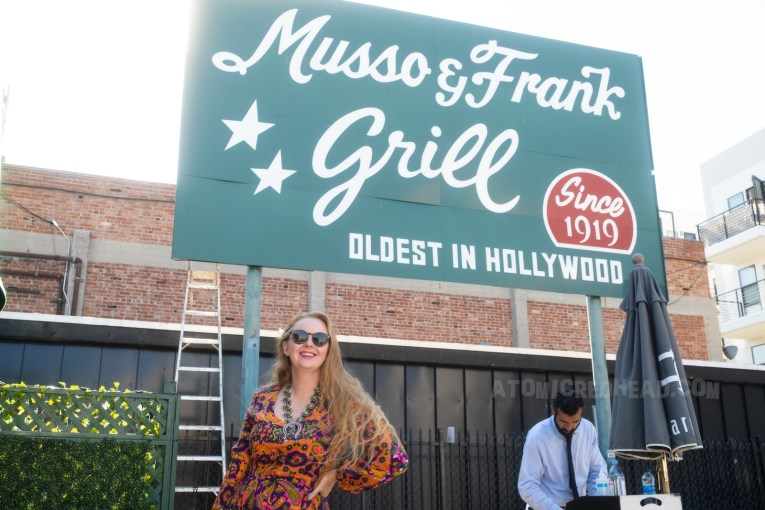 """The large green Musso & Frank's sign in the parking lot, reading """"Musso & Frank's Grill Since 1919 Oldest in Hollywood"""" I stand in front of it wearing a purple, yellow, and orange psychedelic dress."""