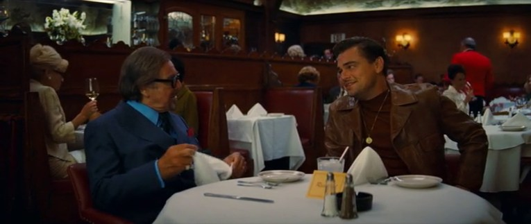 Musso and Frank's as it appears in Once Upon a Time...In Hollywood. Dark wood walls with red leather booths. DiCaprio's Rick sits to the right, while Al Pacino's Schwarz sits on the left.