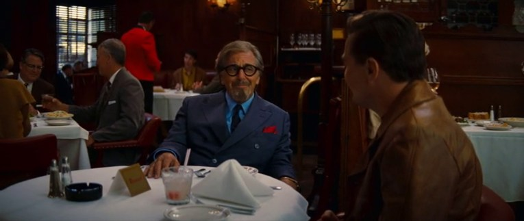 Musso and Frank's as it appears in Once Upon a Time...In Hollywood. View is over Rick's shoulder toward Schwarz, who wears a blue suit, blue shirt, and dark tie, with a red handkerchief in his pocket.