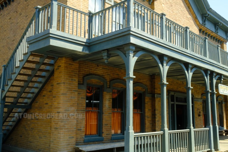 """The saloon as it appears on Universal's backlot, a faux brick exterior with a dark green balcony and porch. A hanging sign out front reads """"Opera House"""""""