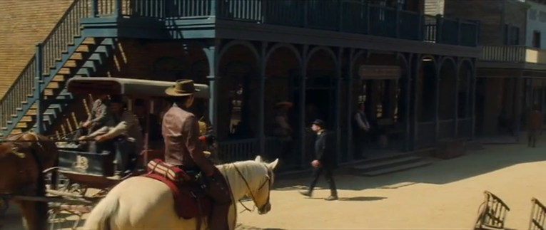 Screencap from Once Upon a Time...In Hollywood, featuring the saloon and Timothy Olyphant riding in from the left on a white horse.