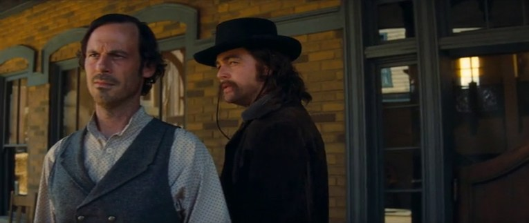 Screencap from Once Upon a Time...In Hollywood, Leonardo DiCaprio, done up in his Lancer duds and make-up looks out from the porch of the saloon.