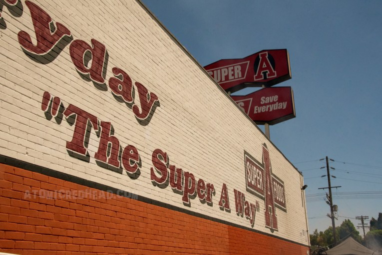"""Super A Foods as it appears today. A cream and burnt orange painted building. Rounded text reads """"The Super A Way"""" along with their """"Super A"""" logo."""