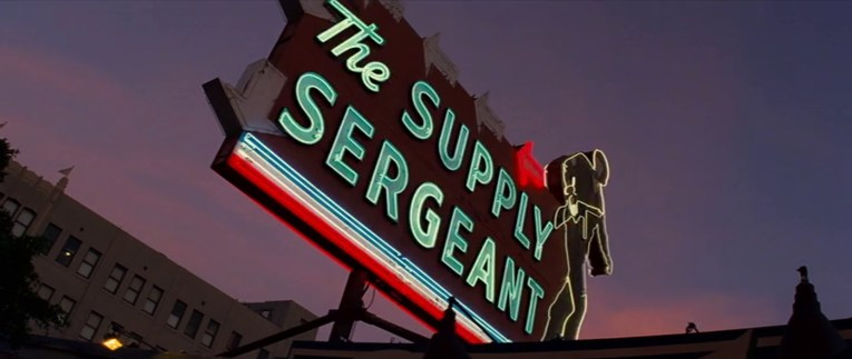 """The Supply Sergeant as it appears in Once Upon a Time...In Hollywood, lit up at night, with a neon soldier, red neon arrows, and blue neon reading """"The Supply Sergeant"""""""