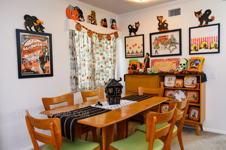 """Overall view of the dining room. On the left is a framed poster for Bob Baker's """"Halloween Spooktacular"""" featuring images of ghosts, and black cat. A window with an abstract print curtain, hanging from the valance is a garland featuring Jack O'lanterns, atop the valance are three black cats with Jack O'lanterns, on the back wall are three frames, two of which feature pieces of vintage table cloths, one with witches the other with haunted houses. In the middle features two die cuts, one of a witch, the other a skeleton with a guitar. Below a secretary features various Halloween decorations."""