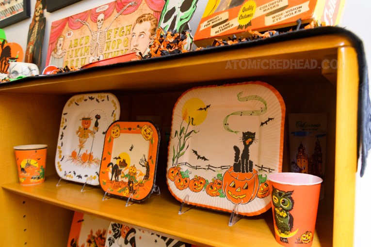 On the shelves of the secretary are various vintage paper plates, one features a scarecrow, another features a black cat atop a Jack O'lantern.