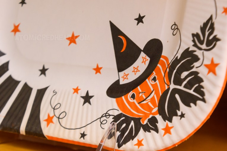 Close-up of one of the paper plates, which features a design of a pumpkin wearing a witch hat with moon and stars on it.