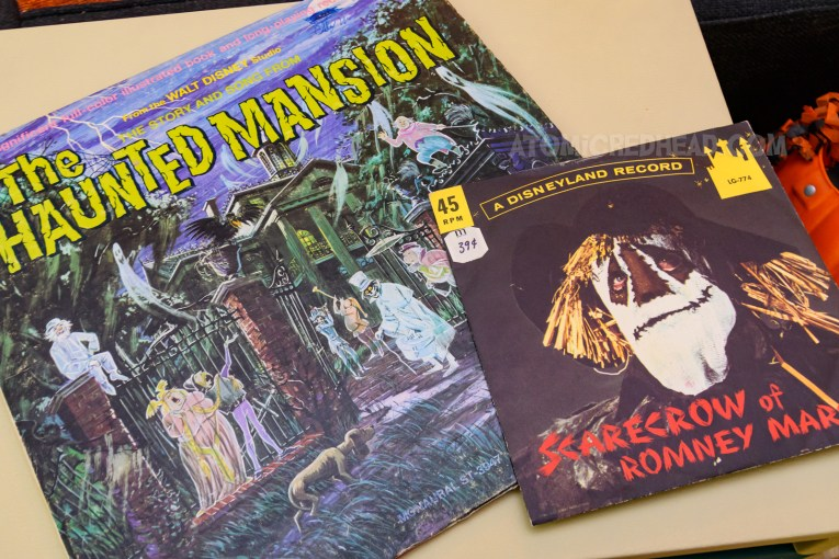 Two records sit atop the record player, one is The Haunted Mansion, featuring an illustration of Disneyland's Haunted Mansion, a southern plantation with a variety of ghosts heading in, the other is a 45 from The Scarecrow of Romney Marsh, featuring a photograph of the title character.