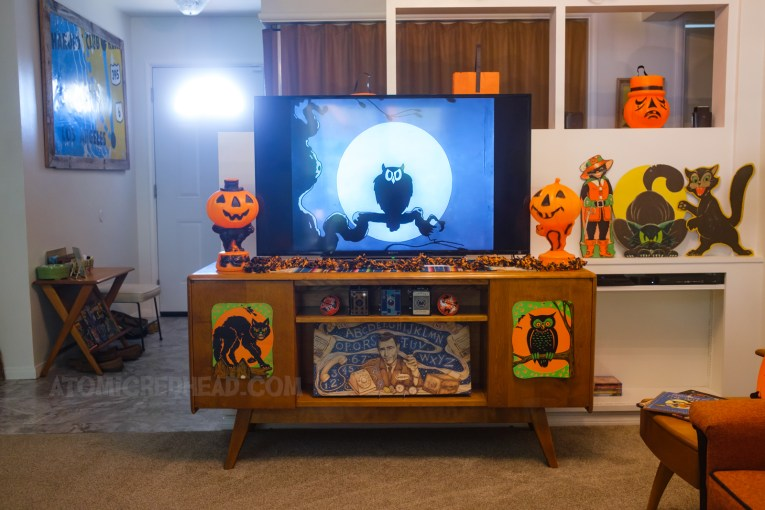 Our entertainment center, with our TV in the center, on screen Disney's Skeleton Dance short, an owl sits on a branch in front of the full moon. On either side are blow mold Jack O'lanterns sitting atop black cats. Hanging on the doors of the entertainment center are die cuts, one of a black cat, the other of an owl. On the shelf below the TV sits a spirit board with Rod Serling of The Twilight Zone.
