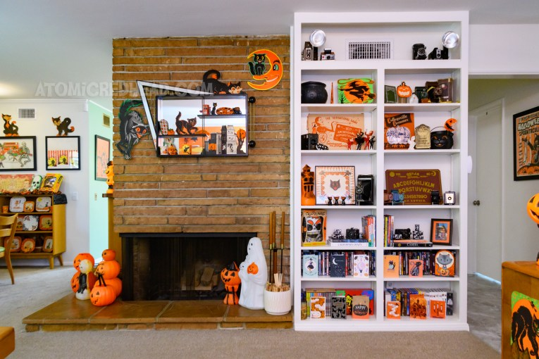 Overall view of a bookcase next to our fireplace. The bookcase contains various Halloween decorations, such as a blow mold haunted house, spirit board, cauldron, die cut witch, and more.