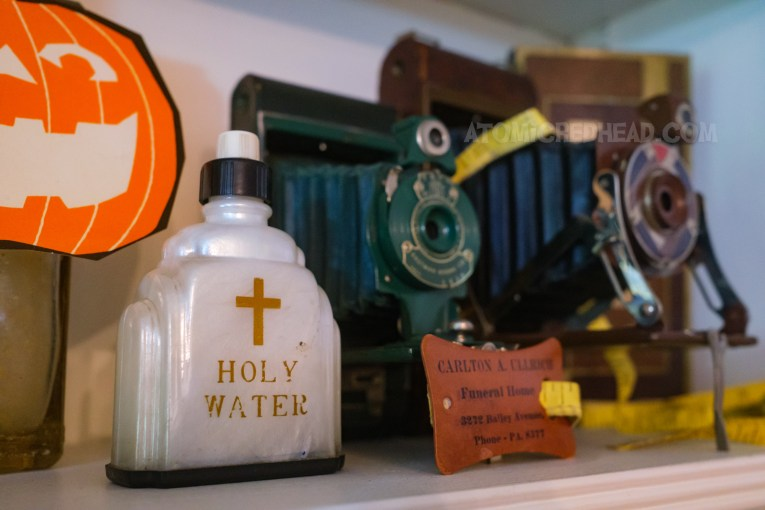 """Close-up of a shelf, featuring a small bottle with gold text reading """"Holy Water"""" next to it is a tape measure for a funeral home."""