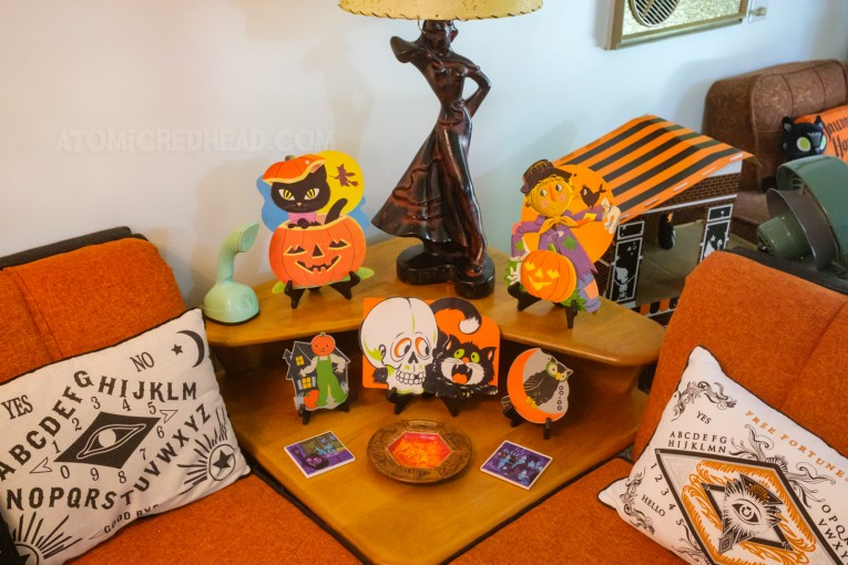 A square table sits between our two couches, atop it sits various Halloween die cuts, including a black cat popping out of a Jack O'lantern, a scarecrow, a black cat with a skull, a smaller scarecrow, and an owl.