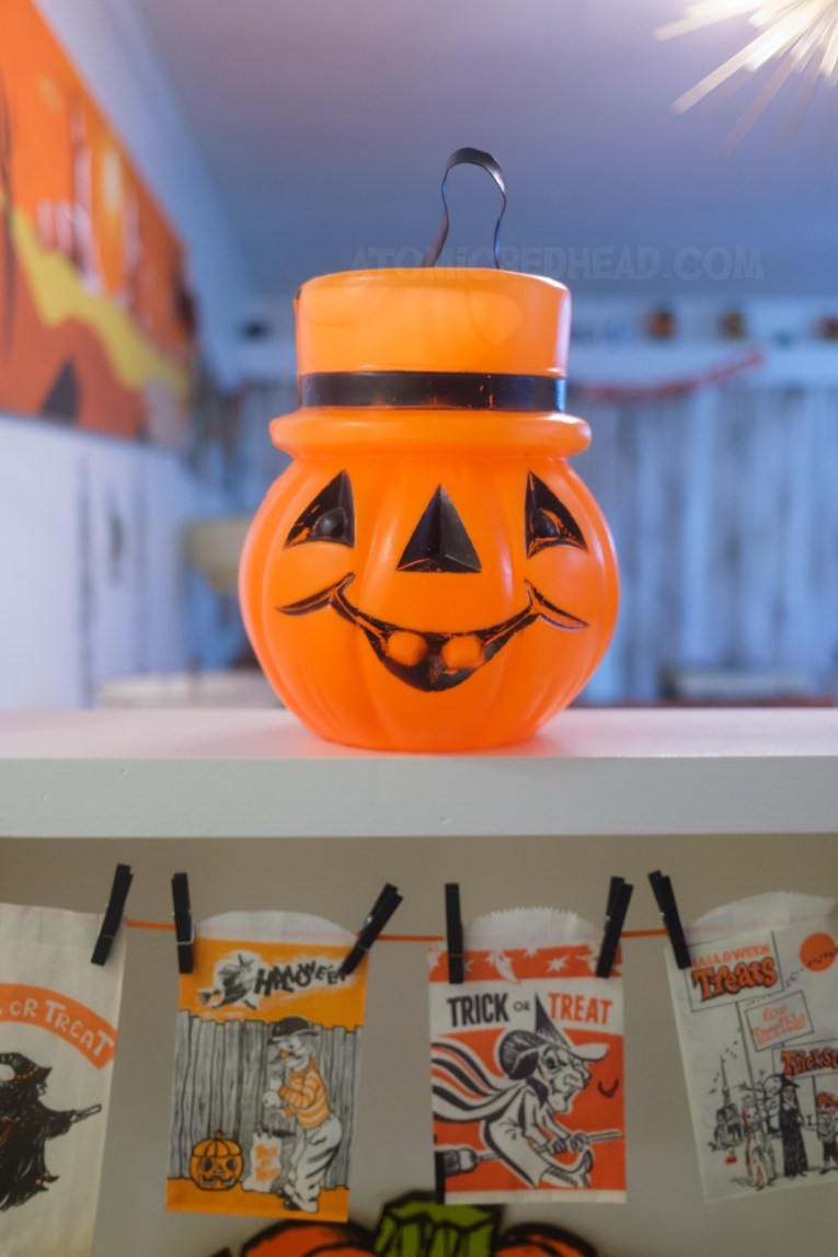 Close-up of a blow mold trick or treat bucket of a Jack O'lantern with a top hat.
