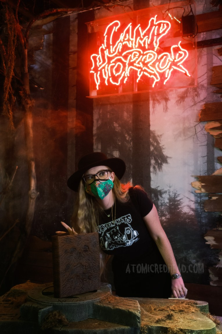 """Myself standing in front of the alter featuring the Necronomicon, a neon sign above reads """"Camp Horror"""""""