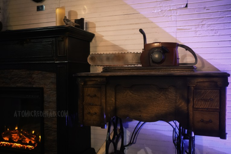 A chainsaw sits atop an antique sewing machine.