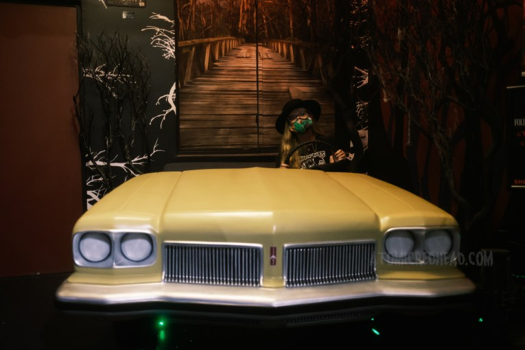 """Myself """"driving"""" the yellow 1973 Oldsmobile Delta 88 Royale with a mural of the bridge painted behind."""