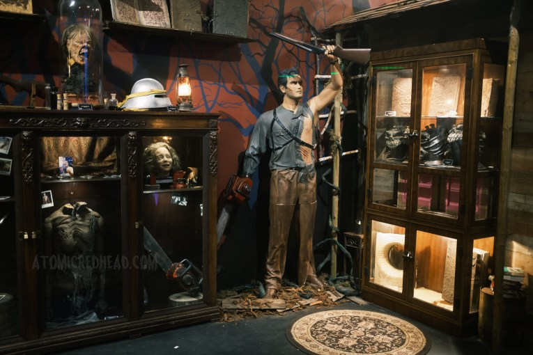 """Overall view of a part of the museum, featuring various display cases housing screen used props, in the middle stands a life size sculpture of Ash from Army of Darkness, holding his """"boomstick"""" high in the air."""