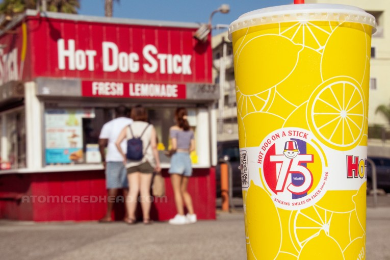 """In the foreground, a yellow cup features the 75th anniversary logo, and text reading """"Sticking Smiles on Faces since 1946."""" the building in the background."""