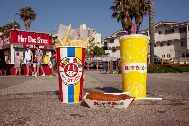 An early evening meal, French fries in a cup, a corndog and a tall cup of lemonade.