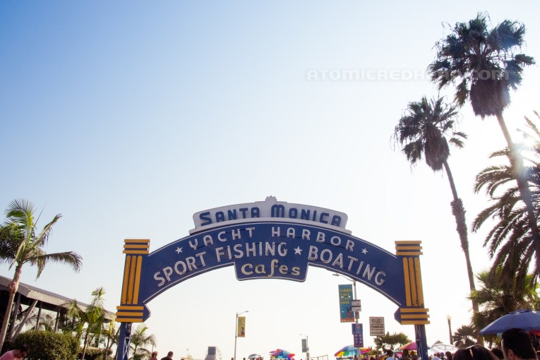 """Santa Monica Pier sign, blue with white letters reading """"Santa Monica Yacht Harbor Sport Fishing Boating Cafes/"""""""