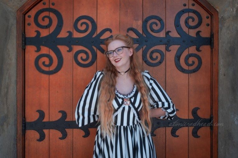 Myself, wearing a black and white stripe dress, a pin featuring the Headless Horseman, Ichabod and Katrina sits at the center of the neckline, a black choker with a rhinestone star charm in the center, standing in front of a large wooden door with black, curling wrought iron details.