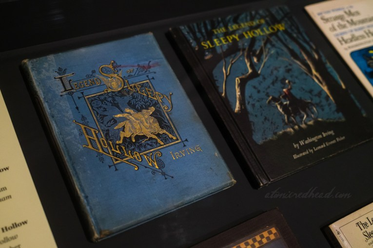 """Two covers of """"The Legend of Sleepy Hollow"""" one blue with black and gold detailing for the title and illustration of the Headless Horseman chasing Ichabod the other is black and blue of the Headless Horseman standing in between leafless trees holding a Jack o'lantern."""