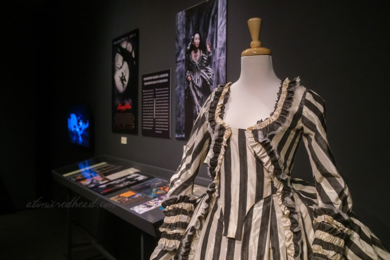 Close-up of a recreation of the iconic black and white stripe dress from Tim Burton's 1999 film version.
