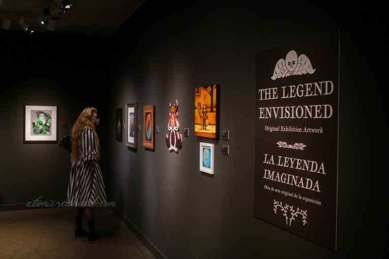 """Art exhibit, a sign reads """"The Legend Envisioned Original Exhibition Artwork"""" various art featuring the Headless Horseman is hung on black walls"""