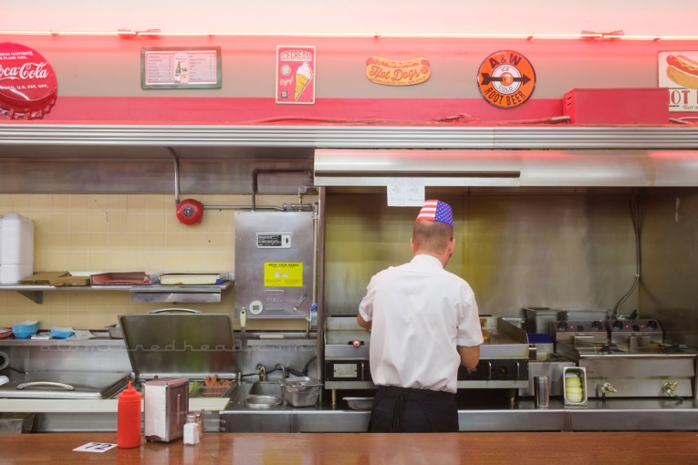 A man works at the cook top behind the counter.