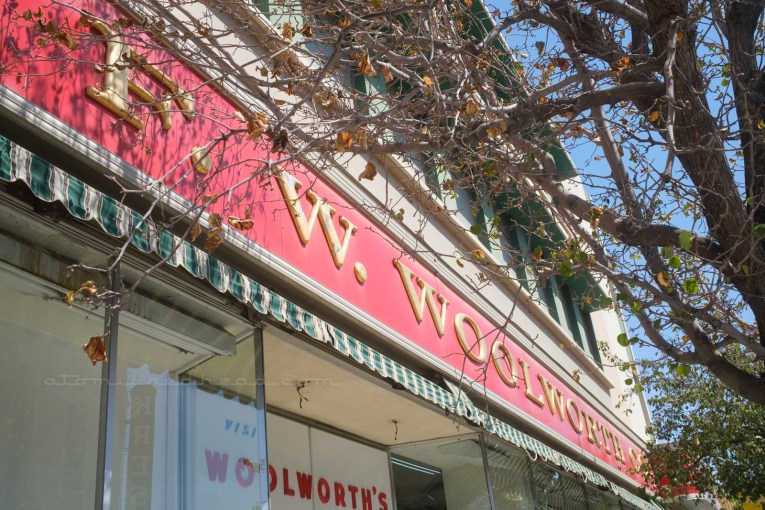 """A long red sign stretches the length of the building reading """"F.W. Woolworth's"""" in large gold letters."""